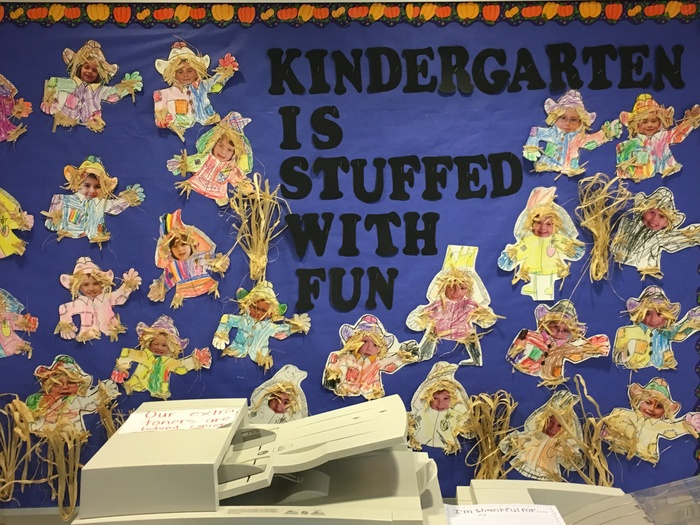 bulletin board in office with kindergarten pictures.